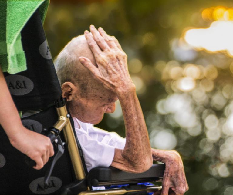 persona mayor mirando hacia abajo en silla de ruedas