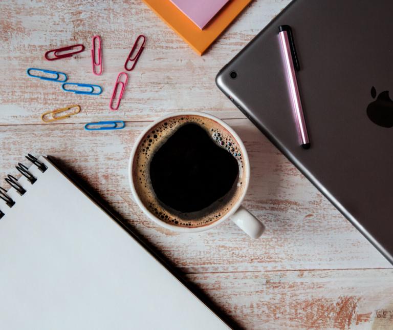 mesa con una taza de cafe, un ordenador, clips,