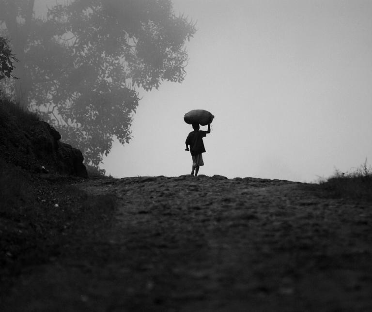 foto en blanco en negro de un niño subiendo una cuesta con un cesto en la cabeza